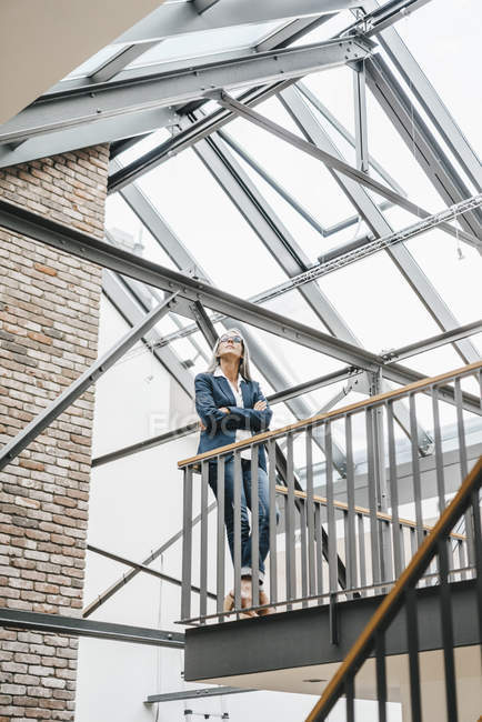 Confident businesswoman with long grey hair standing in loft — Stock Photo
