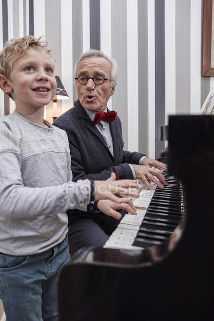 Nonno e nipote che gioca pianoforte e canto — Foto stock