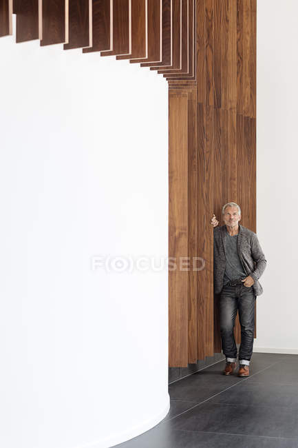 Businessman standing at wooden wall looking up — Stock Photo
