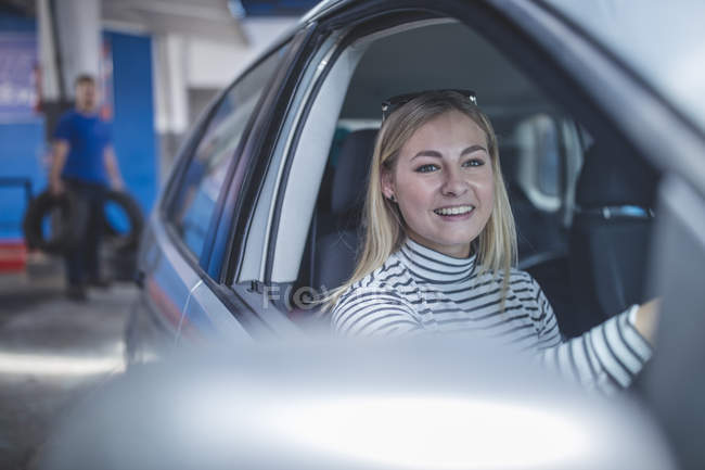 Smiling female customer in car leaving workshop — Stock Photo
