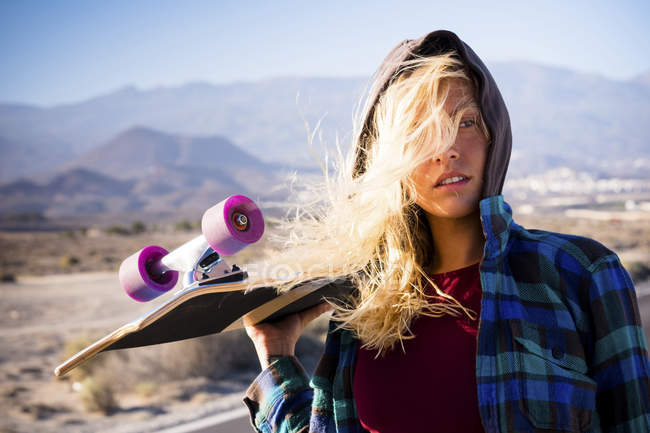 Young beautiful blond girl posing with skateboard outdoors — Stock Photo