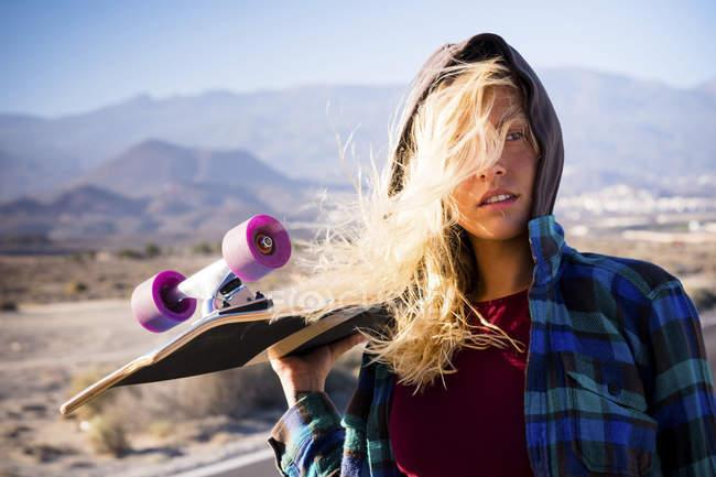 Jeune belle fille blonde posant avec planche à roulettes à l'extérieur — Photo de stock