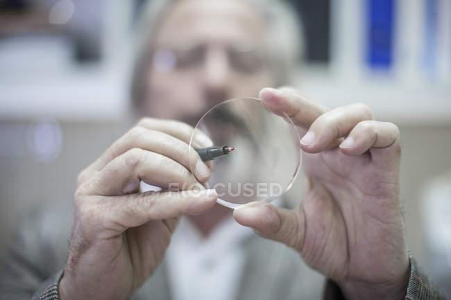 Optometrist looking through eyeglass lens, closeup — Stock Photo