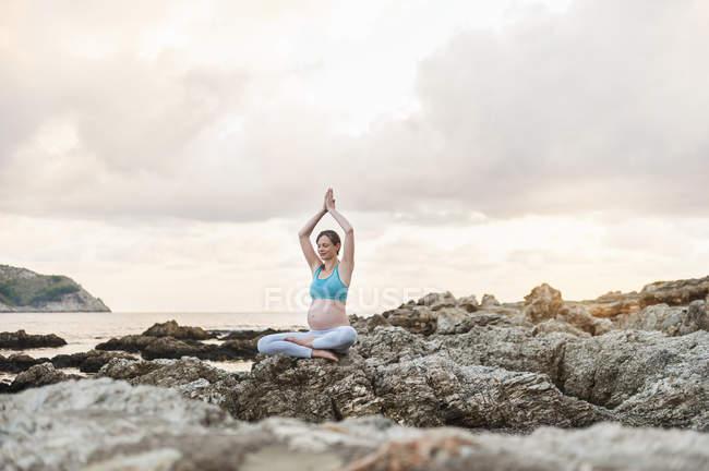 Mujer embarazada practicando yoga en el mar - foto de stock