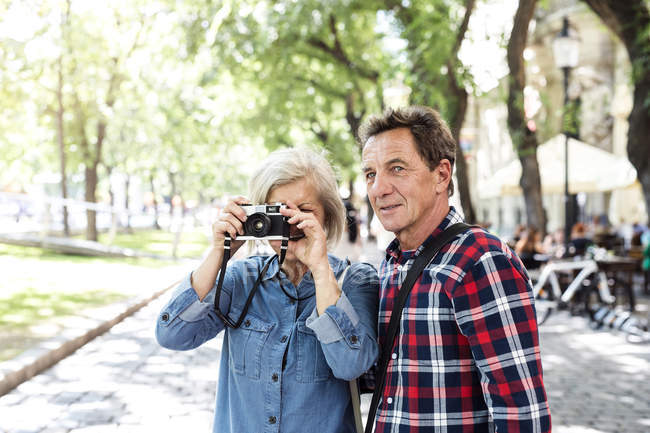 Happy cute senior couple taking photo on camera at park — Stock Photo