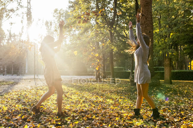 Two best female friends throwing themselves tree leaves in park in autumn — Stock Photo