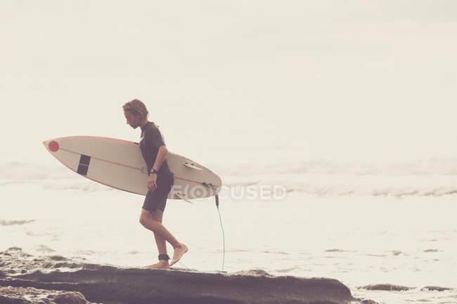 Vista lateral do adolescente carregando prancha na praia — Fotografia de Stock