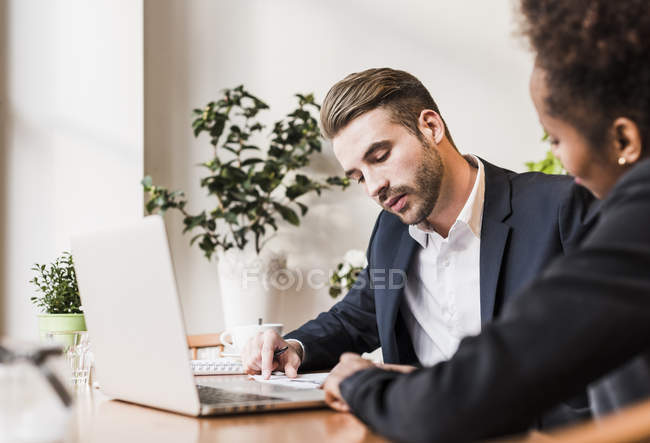 Young businessman and woman using laptop — Stock Photo