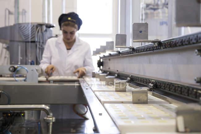 Женщина работает на шоколадной фабрике — стоковое фото