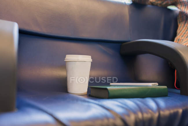 Coffee to go, book and smartphone on seat of a train — Stock Photo