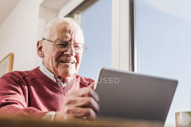 Senior man sitting at home and using laptop — Stock Photo
