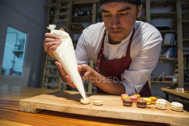 Homem colocando creme com um saco de confeitar em um macaron — Fotografia de Stock
