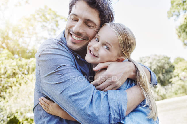 Smiling father and daughter hugging outdoors — Stock Photo
