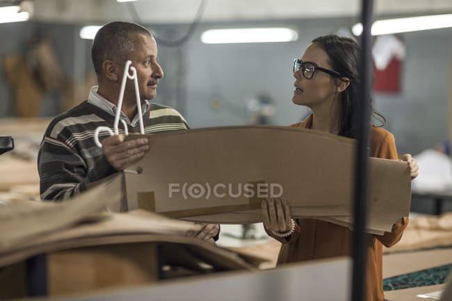 Кравець і модельєр обговорювати різання шаблонів — стокове фото