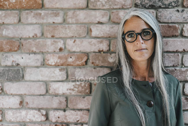 Portrait of businesswoman with long grey hair standing in front of brick wall — Stock Photo