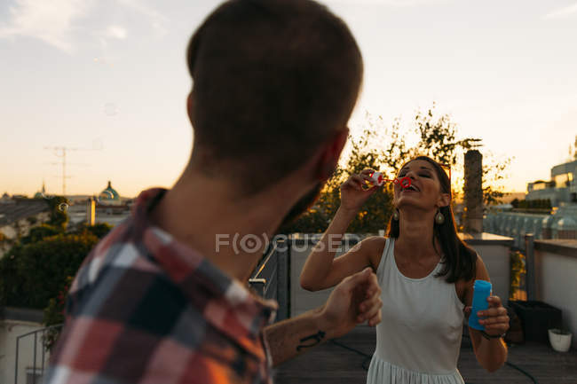 Young woman blowing soap bubbles on roof terrace while her boyfriend watching her — Stock Photo