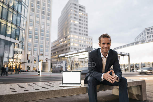 Uomo d'affari seduto su panchina con laptop su Potsdamer Platz — Foto stock