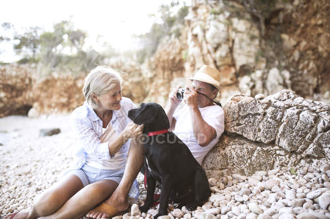 Active cute senior couple taking photo with dog on beach — Stock Photo