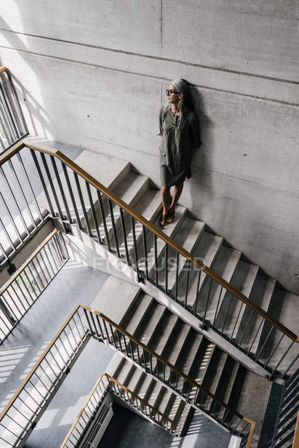 Woman with long grey hair leaning against wall on staircase — Stock Photo