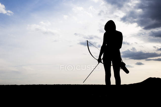 Silhouette of an young sporty archeress standing on a rock — Stock Photo