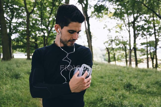 Bel homme sportif caucasien écouteurs à l'aide de téléphone portable au parc — Photo de stock