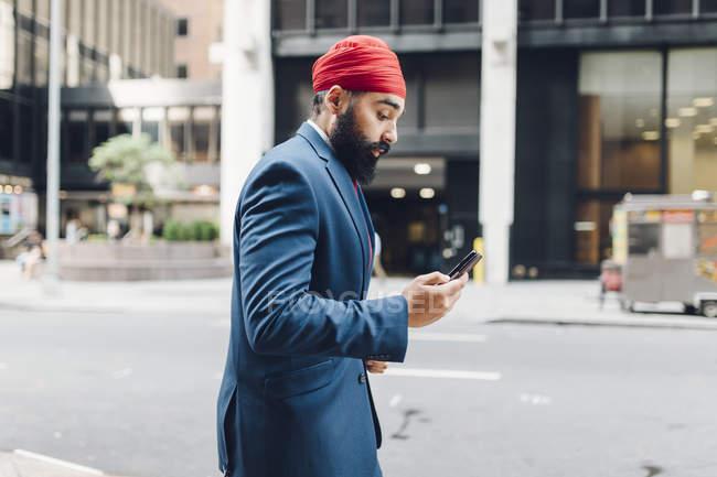 Uomo d'affari indiano che cammina per strada con il cellulare a Manhattan, New York, USA — Foto stock