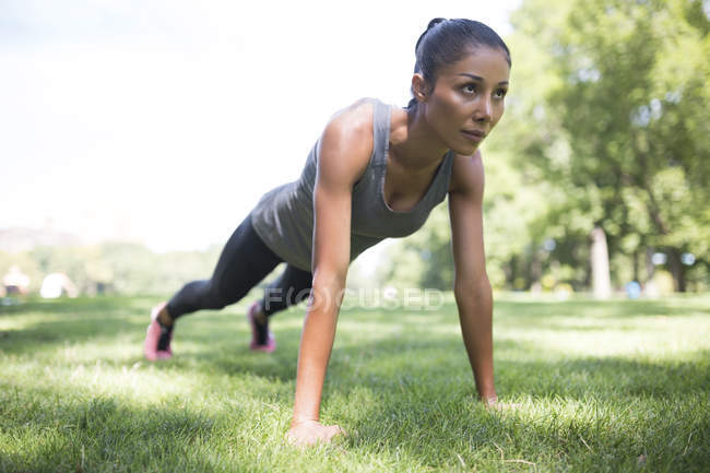Woman doing push-ups on meadow in park — Stock Photo