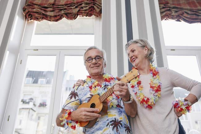 Happy senior couple with man in Hawaiian shirt playing ukulele — Stock Photo