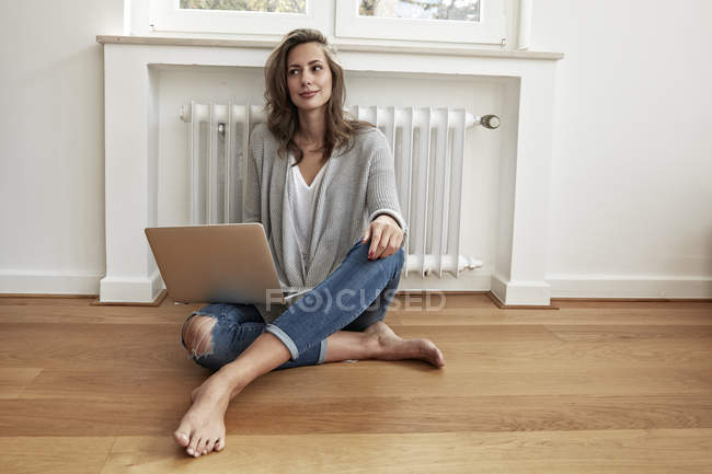 Усміхається жінка, сидячи на підлозі з ноутбука — стокове фото