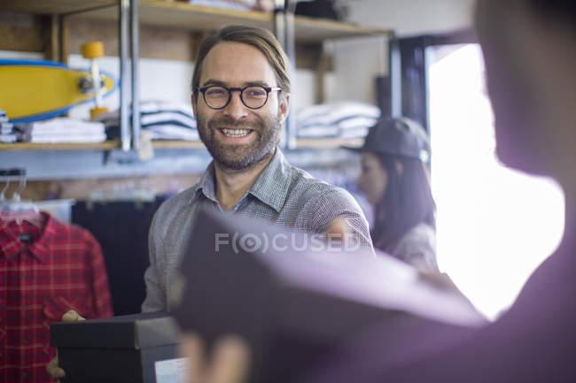 Uomo che compra scarpe in negozio di moda — Foto stock