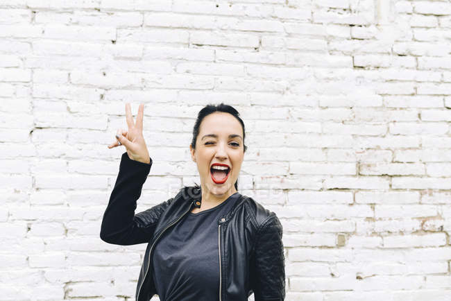 Portrait of young woman in front of brick wall making victory sign — Stock Photo
