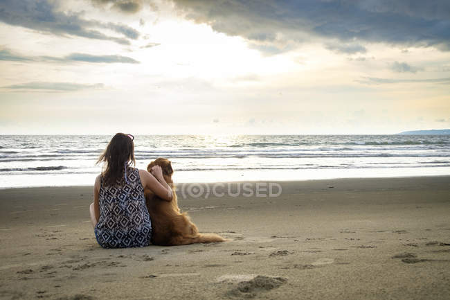 Mexico, Nayarit, Back view of young woman sitting next to her dog at the beach — Stock Photo