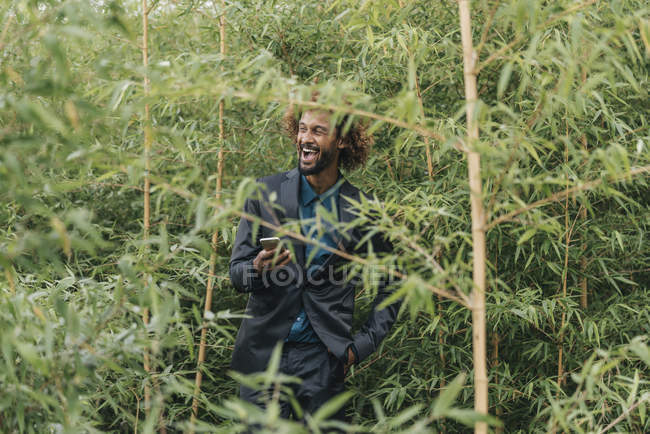 Young businessman with smartphone standing between bushes — Stock Photo