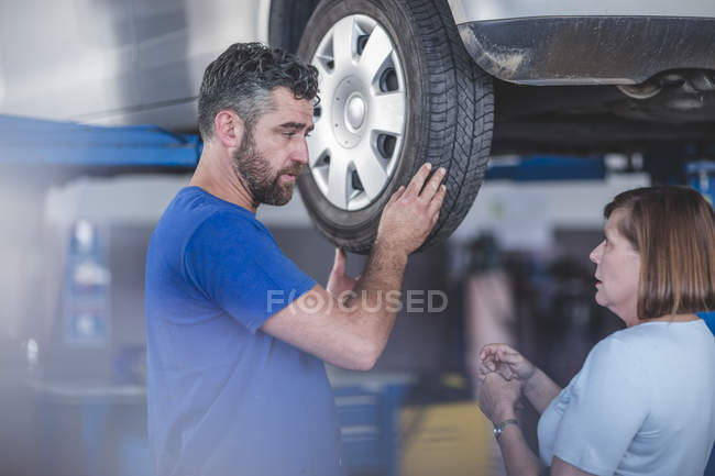Car mechanic in workshop with female customer — Stock Photo