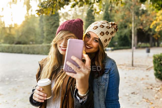 Two best female friends making selfie in park in autumn — Stock Photo