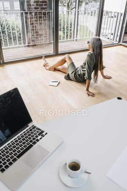 Жінка сидить на підлозі в сучасному офісі з голими ногами — стокове фото