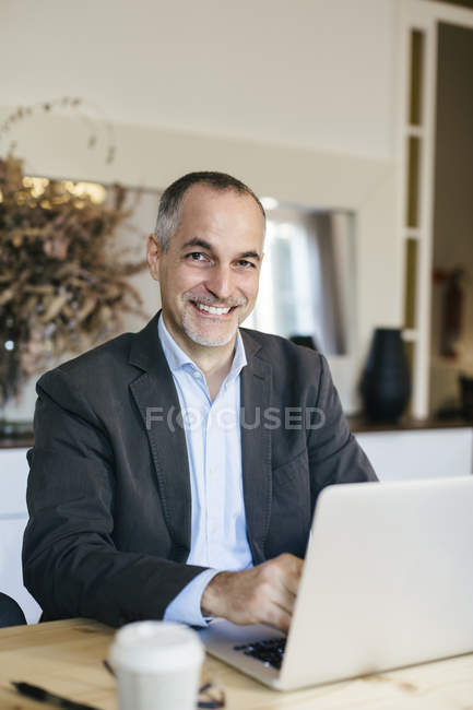 Successful businessman sitting at desk, working on laptop — Stock Photo