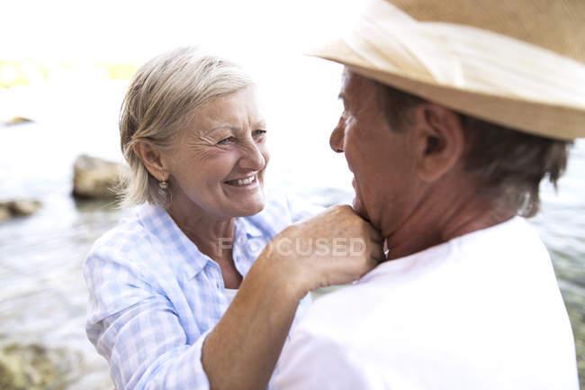 Aktives nettes Senioren-Paar, das sich am Strand umarmt — Stockfoto