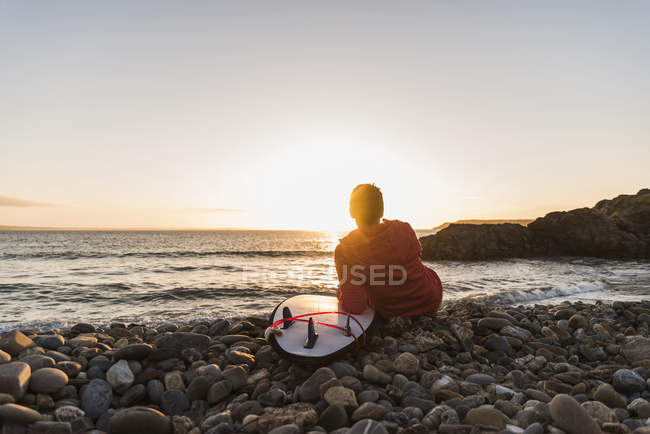 Donna seduta sulla spiaggia al tramonto con tavola da surf — Foto stock