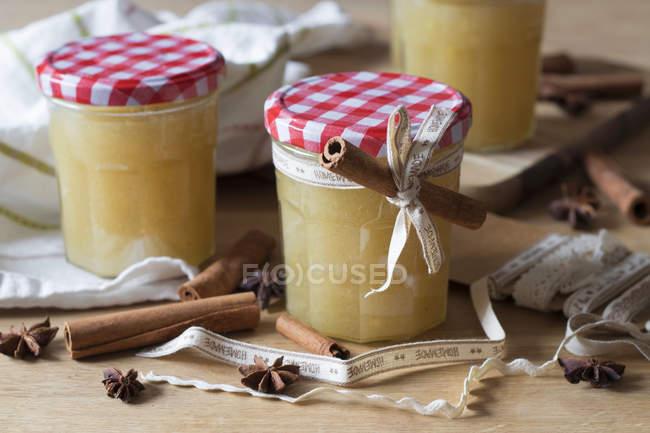 Vue rapprochée des pots de gelée avec des bâtonnets de cannelle et des étoiles d'anis — Photo de stock