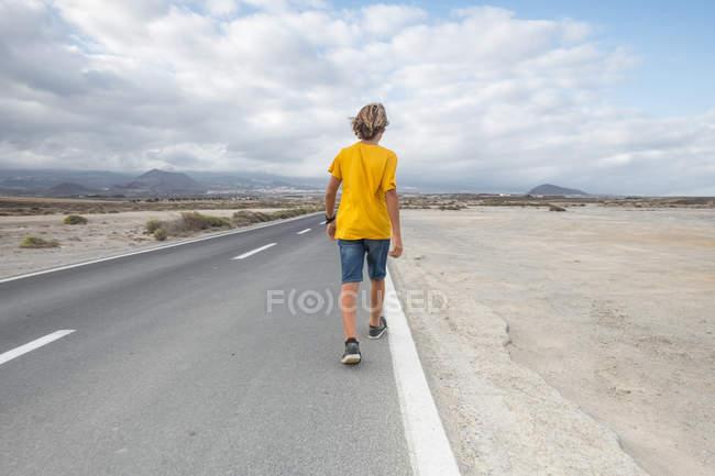 Испания, Тенерифе, мальчик, идущий по пустой проселочной дороге — стоковое фото