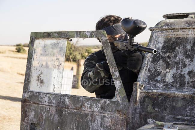 Jogador de paintball, mirando com a arma de paintball, atrás da porta de um carro abandonado — Fotografia de Stock