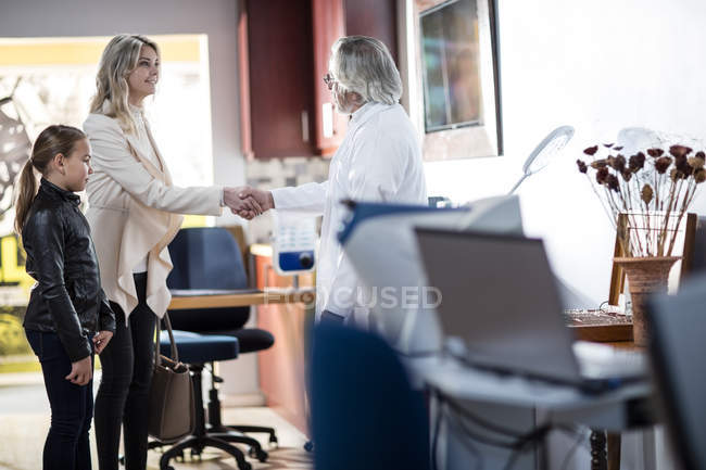 Doctor greeting patients in medical practice — Stock Photo
