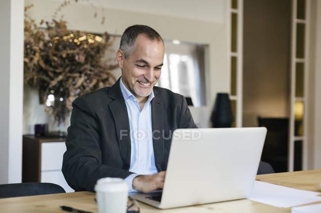 Empresário bem sucedido, sentado na mesa e trabalhando no laptop — Fotografia de Stock