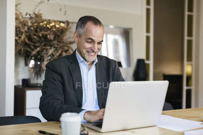 Successful businessman sitting at desk and working on laptop — Stock Photo