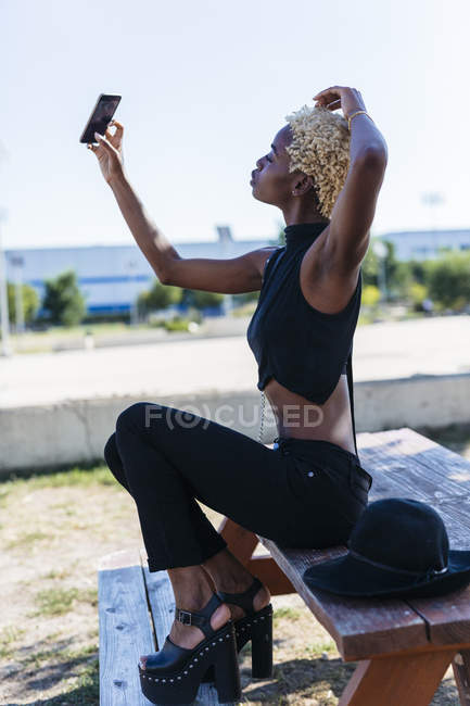 Young woman posing with cell phone outdoors — Stock Photo