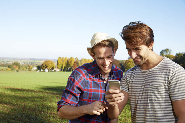 Young men sharing smartphone in the countryside — Stock Photo