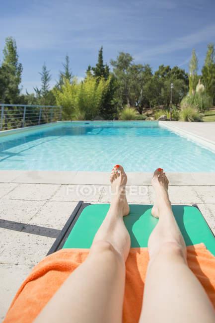 Mulher de bronzeamento na piscina — Fotografia de Stock