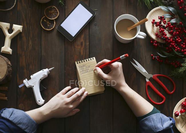 Frauenhände schreiben an ihrem Schreibtisch im Advent auf Notizblock — Stockfoto