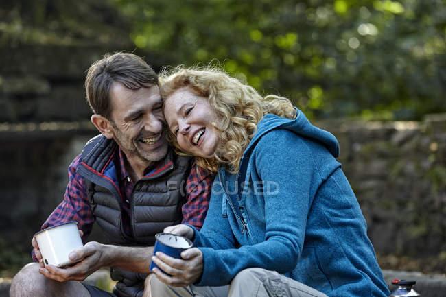 Brautpaar sitzt in der Natur mit Kaffeetassen — Stockfoto
